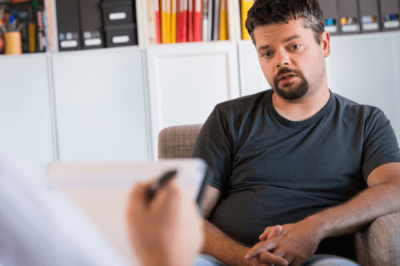 A dad closely listening to the therapist in parenting counseling in Louisville, KY